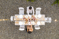 Italy, Tuscany, Siena, top view of young couple dining al fresco clinking red wine glasses - FBAF00185