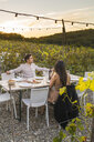 Italy, Tuscany, Siena, young couple having dinner in a vineyard - FBAF00188