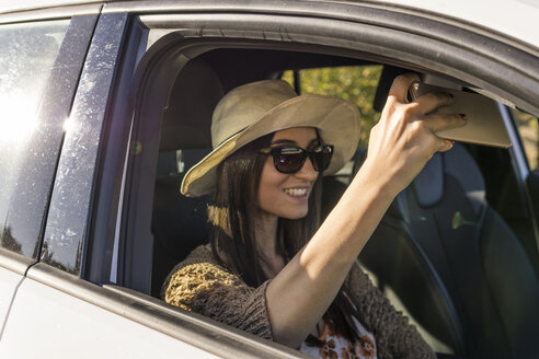 Smiling young woman sitting in a car taking selfie with cell phone - FBAF00191