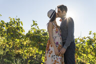 Italy, Tuscany, Siena, young couple kissing in a vineyard - FBAF00200
