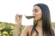 Italy, Tuscany, Siena, young woman drinking red wine in a vineyard at sunset - FBAF00209