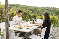 Italy, Tuscany, Siena, young couple having dinner in a vineyard - FBAF00212
