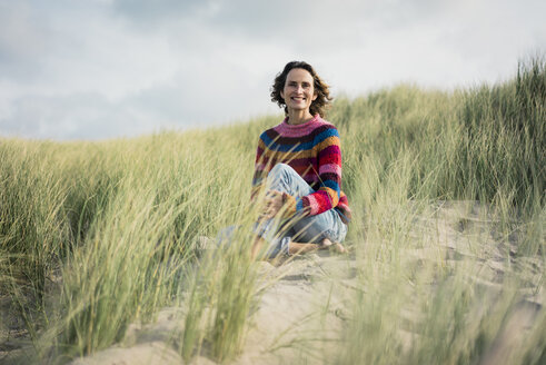 Mature woman relaxing on the beach, sitting in the dunes - MOEF01573