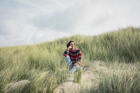 Mature woman relaxing on the beach, sitting in the dunes - MOEF01579