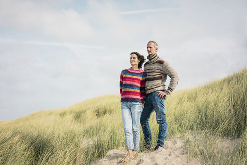 Mature couple standing in the dunes, with arms around - MOEF01582