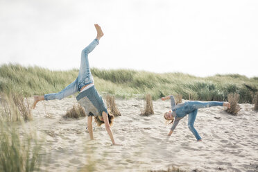 Mother and daughter having fun, cartwheeling on the beach - MOEF01585