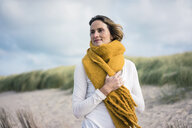 Mature woman relaxing in the dunes, enjoying the wind - MOEF01588