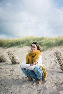 Mature woman crouching in the dunes, enjoying the wind - MOEF01591