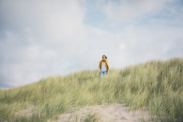 Mature woman relaxing in the dunes, enjoying the wind - MOEF01594