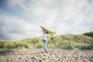 Mature woman holding flapping scarf in the wind, relxiang in the dunes - MOEF01597