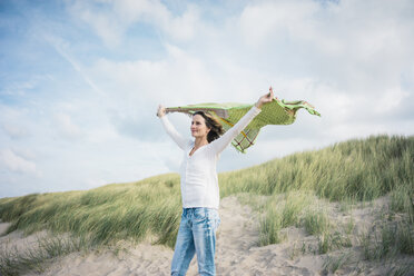 Mature woman holding flapping scarf in the wind, relxiang in the dunes - MOEF01600