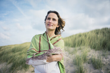 Mature woman standing in the dunes, looking at distance - MOEF01603
