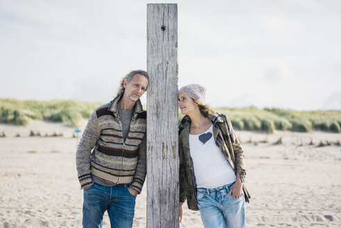 Mature couple on the beach, leaning on wood pole - MOEF01609