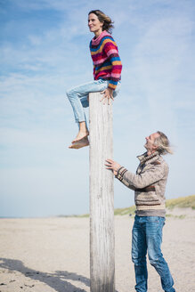Mature man helping woman to climb a wood pole on he beach - MOEF01615