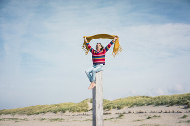 Mature woman sitting on a wood pole on the beach, holding scarf in the wind - MOEF01618