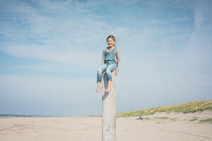 Little girl on the beach sitting on a pole - MOEF01621