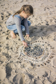 Little girl making a heart from seashells on the beach - MOEF01624