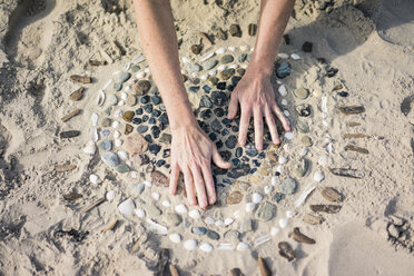 Mature woman making a heart from seashells on the beach - MOEF01627