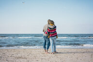 ture couple standing on the beach with arms around, looking at the sea - MOEF01633