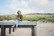 Mature woman sitting on boardwalk at the beach, using laptop - MOEF01639