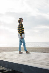 Mature woman standing on boardwalk at the beach, holding laptop - MOEF01642