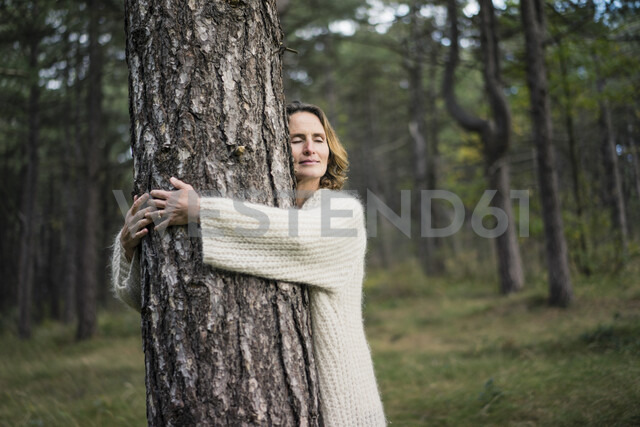 Woman hugging tree in forest - MOEF01648 - Robijn Page/Westend61