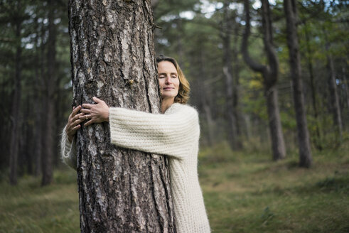 Woman hugging tree in forest - MOEF01648