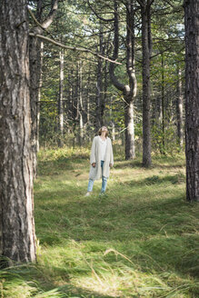 Serene woman standing in the forest - MOEF01651