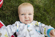 Overhead portrait of cute baby boy making face while lying on grassy field at backyard - CAVF56015