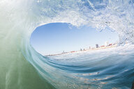 Buildings seen through wave in sea against clear sky - CAVF56033