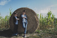 Brothers standing by hay bale in corn field against sky - CAVF56039
