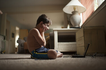 Side view of excited boy looking at laptop computer while sitting on carpet - CAVF56099