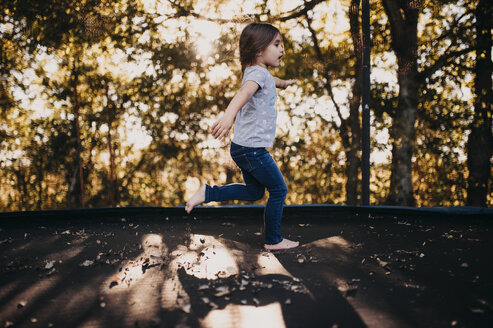 Side view of girl running on footpath by trees - CAVF56123