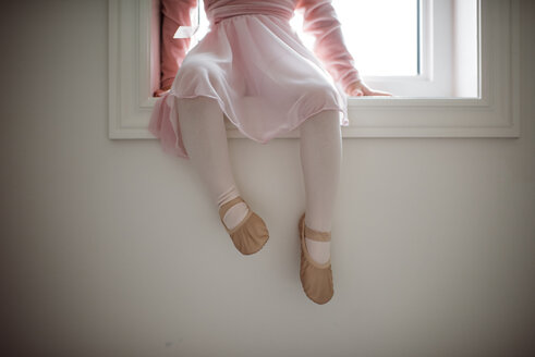 Low section of girl in ballet costume sitting on window sill at home - CAVF56138