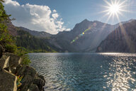 Scenic view of lake against mountains in forest during sunny day - CAVF56147