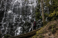 Side view of woman standing by Ramona Falls in forest - CAVF56207