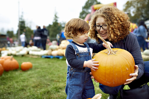 Mother with son holding pumpkin at farm - CAVF56222