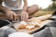 Low section of man cutting loaf of bread while sitting on picnic blanket - CAVF56267