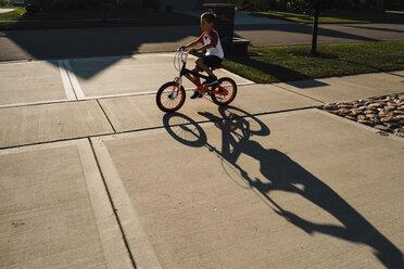 Boy riding bicycle on sidewalk - CAVF56291