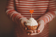 Midsection of woman holding cupcake while standing at home - CAVF56381
