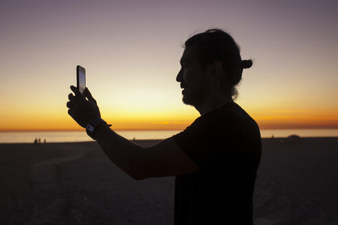 Side view of man photographing with smart phone against dramatic sky at beach during sunset - CAVF56399