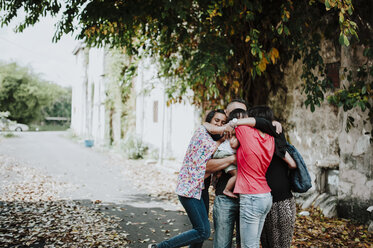 Happy family embracing while standing on street - CAVF56408