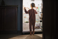 Rear view of girl standing by refrigerator at home - CAVF56417