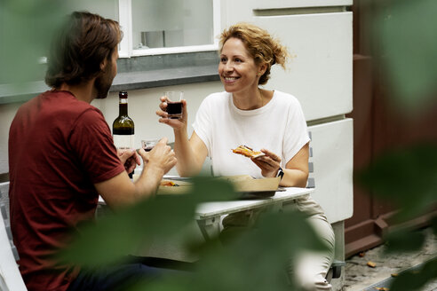 Happy couple sitting in the garden, eating pizza, drinking wine - HHLMF00568