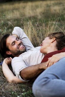 Happy couple cuddling, lying on a meadow - HHLMF00571
