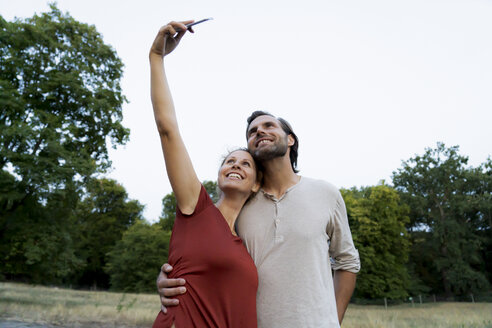 Happy couple taking selfies outdoors - HHLMF00592