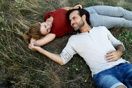 Happy couple cuddling, lying on a meadow - HHLMF00613