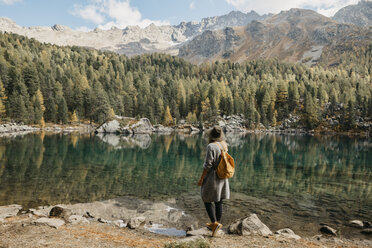 Switzerland, Engadin, woman on a hiking trip standing at lakeside in mountainscape - LHPF00135