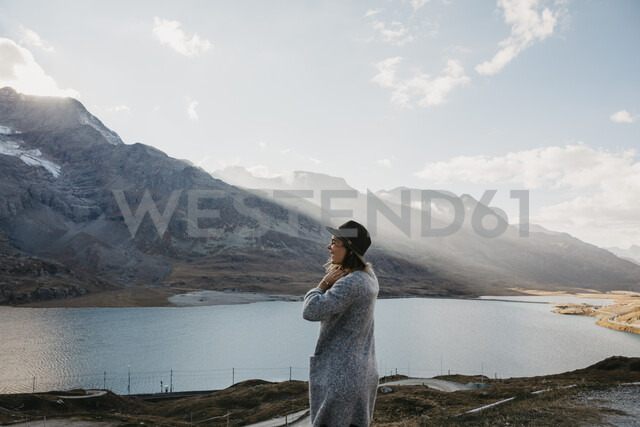 Switzerland, Engadin, woman standing at lakeside in mountainscape - LHPF00138 - letizia haessig photography/Westend61