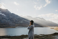 Switzerland, Engadin, woman standing at lakeside in mountainscape - LHPF00138